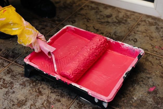Uma jovem pinta o interior de rosa com um rolo de close-up. reparação do interior.