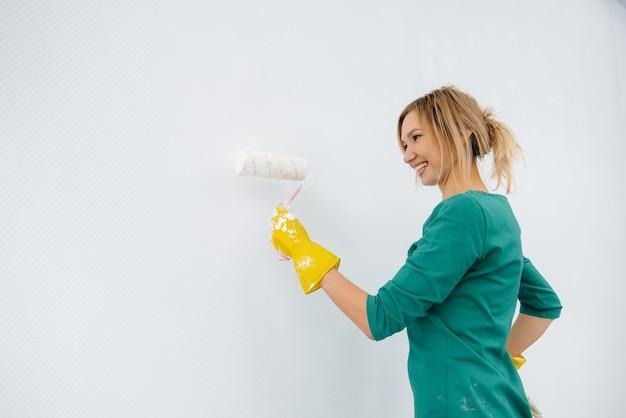 Uma jovem pinta uma parede branca com um rolo. reparação do interior.