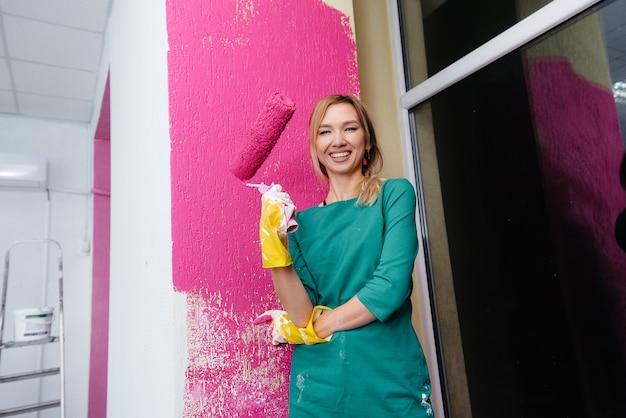 Uma jovem pinta uma parede branca em rosa com um close-up de rolo. reparação do interior.