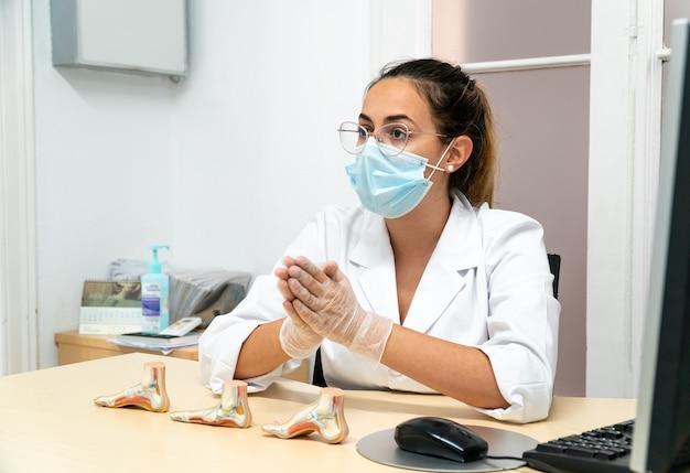 Uma jovem podóloga mascarada sentada em seu consultório enquanto explica o diagnóstico para sua paciente