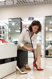 Uma jovem ponderada escolhe entre sapatos vermelhos, brancos e pretos de salto alto.