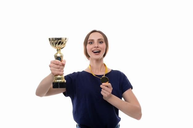 Uma jovem posa com a taça do vencedor e a medalha de ouro em um fundo branco