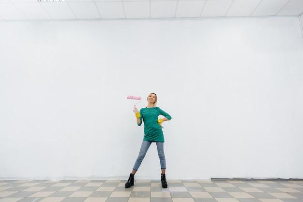 Uma jovem posa com um rolo na frente de uma parede branca. reparação do interior.