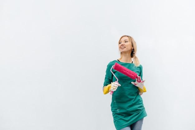Uma jovem posa com um rolo rosa antes de pintar uma parede branca. reparação do interior.