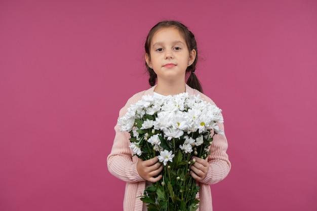 Uma jovem posa em um fundo rosa com flores nas mãos crisântemo