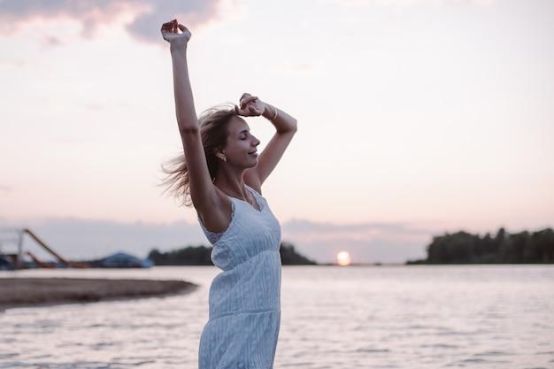 Uma jovem posa no contexto de uma foto de paisagem uma bela loira feliz em um branco ...
