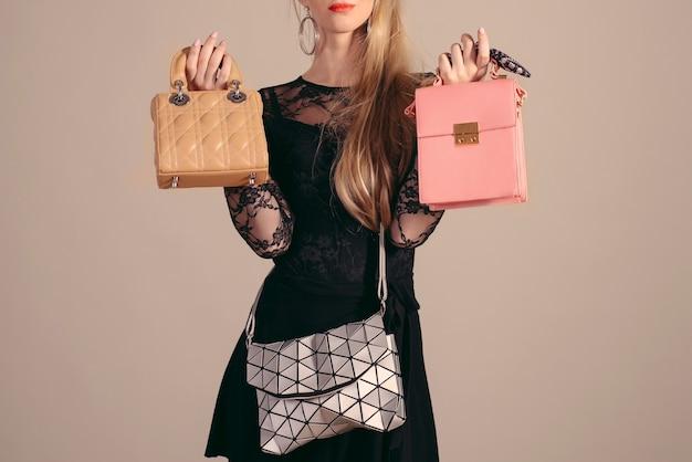 Uma jovem posando com um vestido preto e bolsas