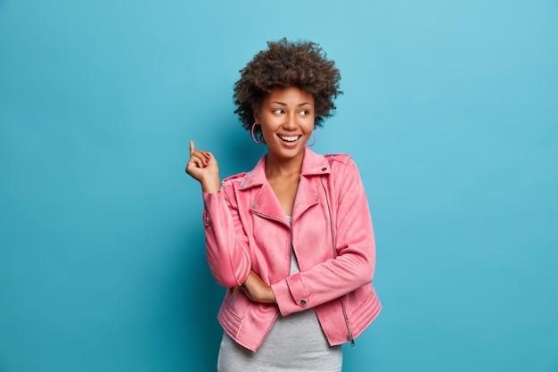 Uma jovem positiva de pele escura ri positivamente, tem uma expressão facial alegre, levanta a mão e é entretida por amigos, usa uma jaqueta elegante