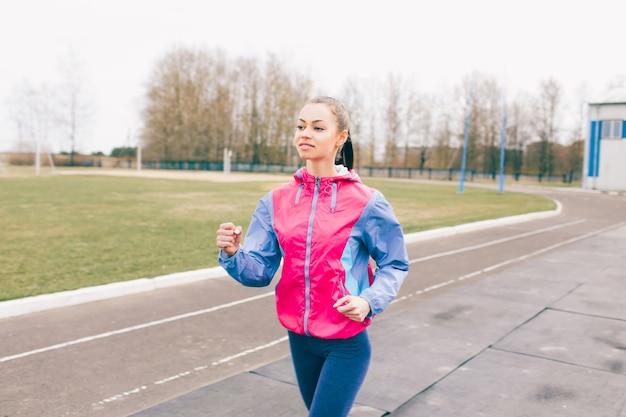 Uma jovem pratica esportes fazendo uma corrida ao redor do estádio