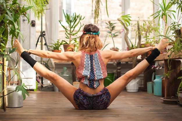 Uma jovem pratica ioga entre a selva urbana. menina no asanas da ioga e no espaço do close-up e da cópia de pilates em casa.