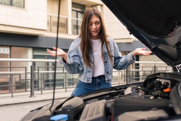Uma jovem preocupada está usando um telefone para explicar ao mecânico o problema com um carro que ela possui.