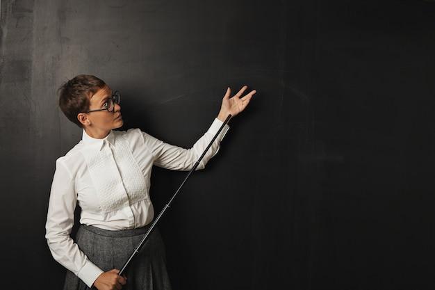 Uma jovem professora branca, séria, com blusa de botão e saia de tweed parada em um quadro negro segurando um ponteiro