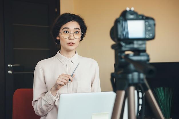 Uma jovem professora está explicando algo durante uma aula online usando um laptop
