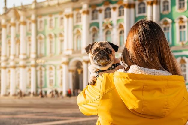 Uma jovem proprietária com uma jaqueta amarela segura um pug nos braços em uma praça turística em petersburgo