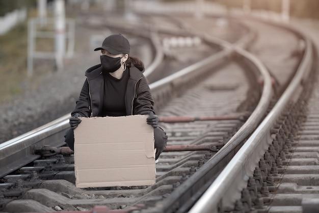 Uma jovem protestante está sentada na ferrovia, segurando um cartaz com um lugar para assinar.