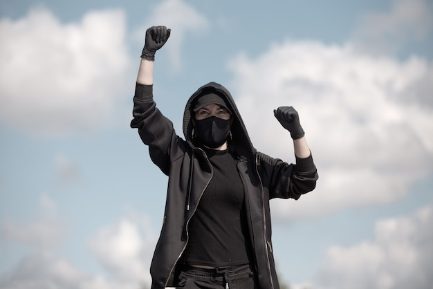 Uma jovem protestante levanta a mão no ar contra um céu nublado
