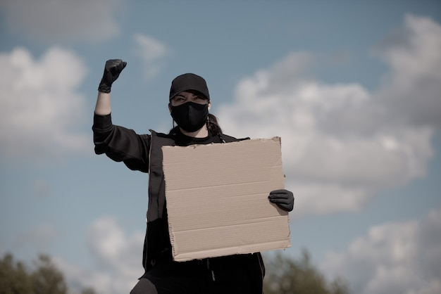 Uma jovem protestante levanta a mão no ar, segurando um pôster com a inscrição