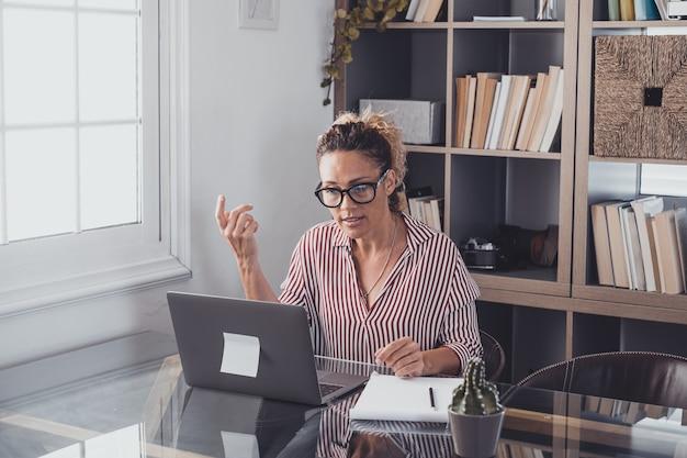 Uma jovem que trabalha em casa no escritório com laptop e notebook tomando notas falando em uma videoconferência. uma empresária ligando e se comunicando