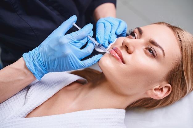 Uma jovem relaxada está cuidando do rosto e se inscrevendo para injeções de beleza na cosmetologista