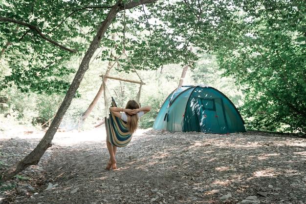 Uma jovem relaxando em uma rede no bosque.