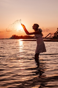 Uma jovem respinga água foto de uma bela loira feliz esbelta em um vestido de verão e um canudo ...