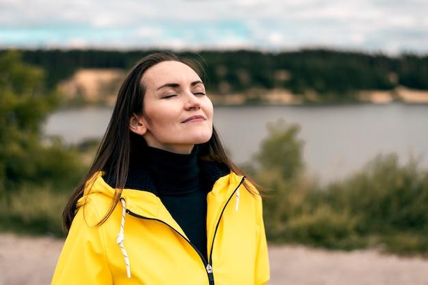 Uma jovem respira o ar fresco do outono na natureza perto do lago da floresta, com uma capa de chuva amarela