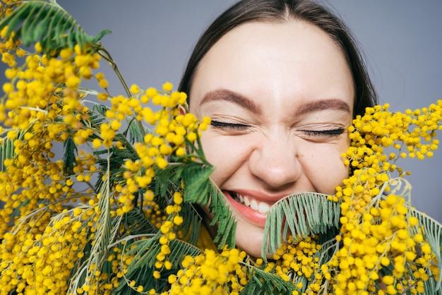 Uma jovem rindo cheira uma mimosa amarela perfumada, flores da primavera