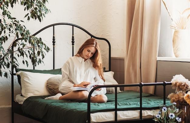 Uma jovem romântica com cabelo comprido se senta em uma cama com um livro. lendo na cama