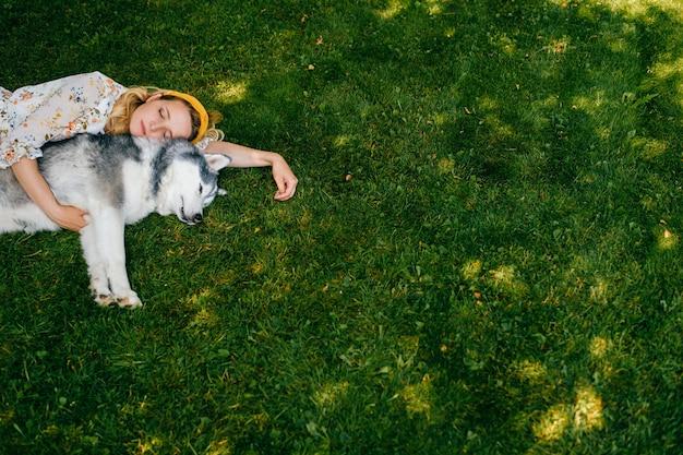Uma jovem romântica deitada com um cachorro na grama