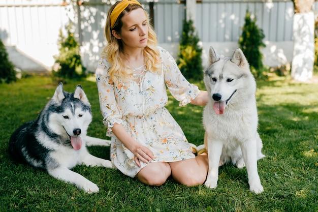 Uma jovem romântica posando com dois cachorros na grama