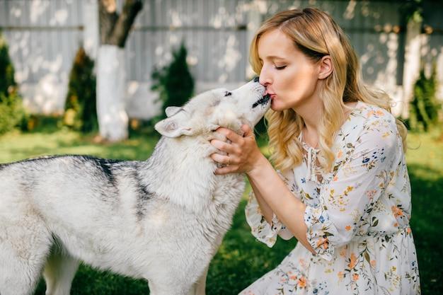 Uma jovem romântica posando com um cachorro na grama