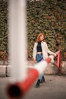 Uma jovem ruiva bonita está andando na rua, ela está vestida com jeans e uma camisa bege. linda garota vestida em estilo casual com um sorriso no rosto
