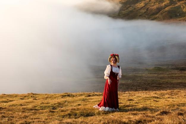 Uma jovem ruiva em roupas antiquadas com uma saia vermelha brilhante fica no campo de grama nas montanhas. f