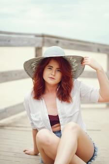 Uma jovem ruiva em um grande chapéu redondo sentado na areia na praia