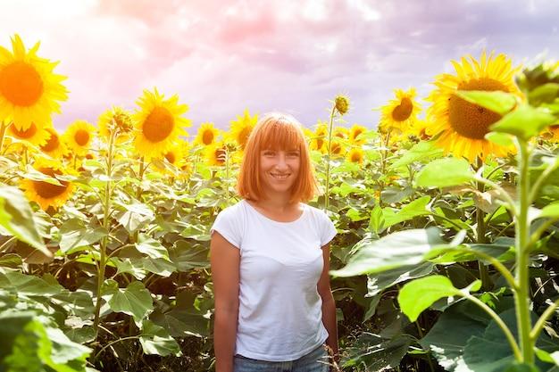 Uma jovem ruiva em uma camiseta branca e jeans sorri e gosta de uma caminhada de verão em um campo de girassóis contra um céu azul em um dia quente de verão