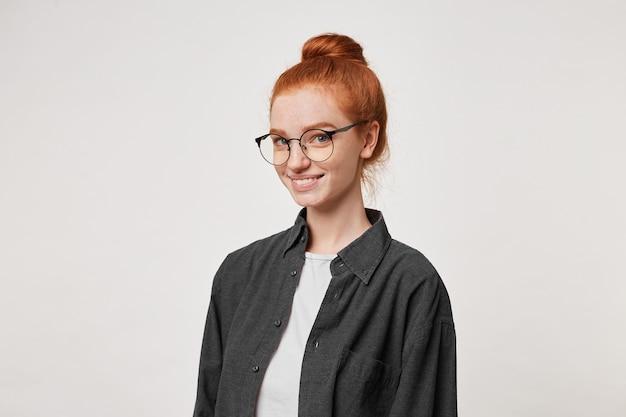 Uma jovem ruiva fica olhando para a câmera através dos óculos.