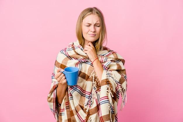 Uma jovem russa enrolada em um cobertor bebendo café sente dor de garganta devido a um vírus ou infecção.