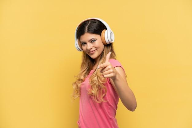 Uma jovem russa isolada em um fundo amarelo ouvindo música