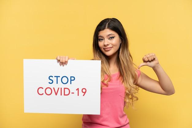 Uma jovem russa isolada em um fundo amarelo segurando um cartaz com o texto pare covid 19 com um gesto orgulhoso