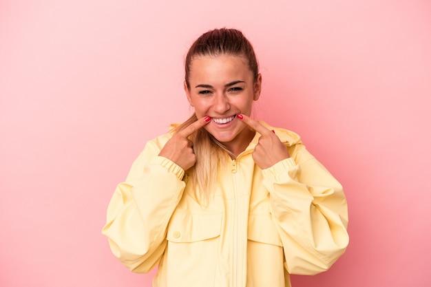 Uma jovem russa isolada em um fundo rosa sente-se orgulhosa e autoconfiante, exemplo a seguir.