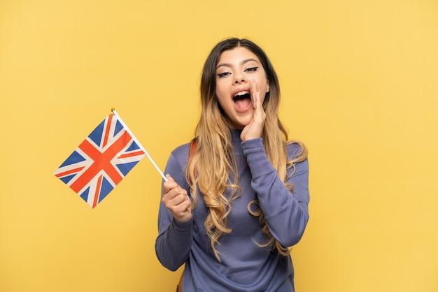 Uma jovem russa segurando uma bandeira do reino unido, isolada em um fundo amarelo, com expressão facial de surpresa e choque