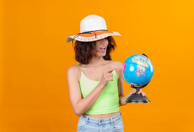 Uma jovem satisfeita com cabelo curto em um top verde recortado com chapéu de sol apontando para um globo com o dedo indicador