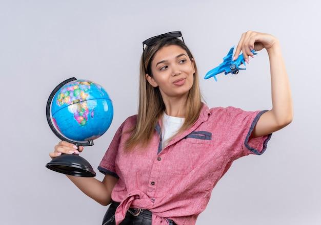 Uma jovem satisfeita com uma camisa vermelha e óculos escuros segurando um globo enquanto pilotava um avião de brinquedo azul em uma parede branca