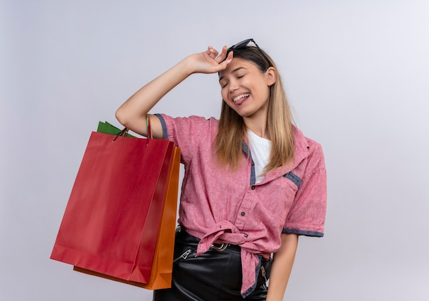 Uma jovem satisfeita, vestindo uma camisa vermelha, segurando sacolas de compras coloridas com as mãos na cabeça em uma parede branca