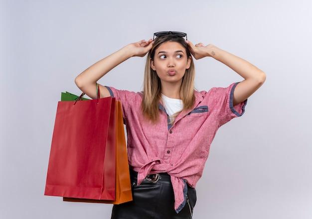 Uma jovem satisfeita, vestindo uma camisa vermelha, segurando sacolas de compras coloridas, olhando de lado em uma parede branca
