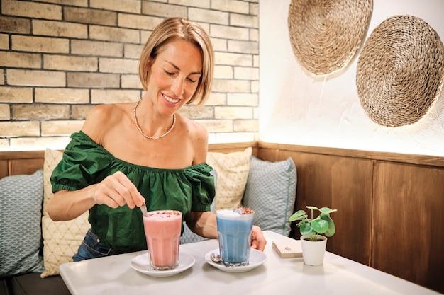Uma jovem saudável bebendo smoothies coloridos