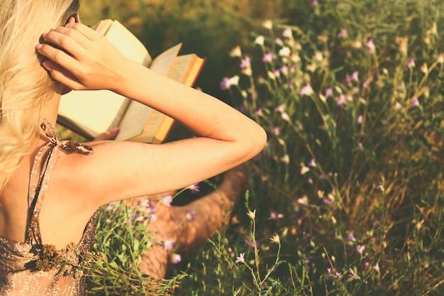 Uma jovem se senta de costas para a câmera e lê um livro em um campo de flores silvestres. conceito de verão outono