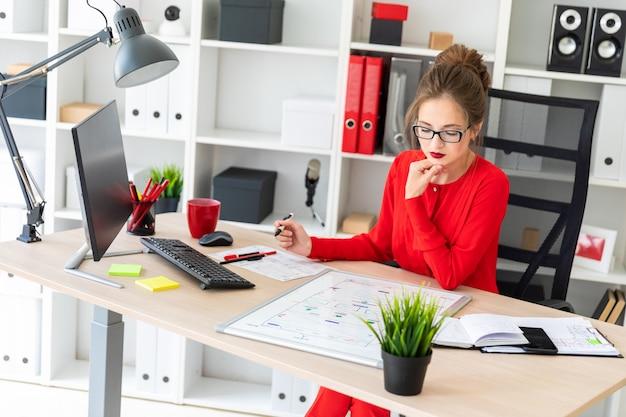 Uma jovem se senta em uma mesa no escritório, segura um marcador na mão e trabalha