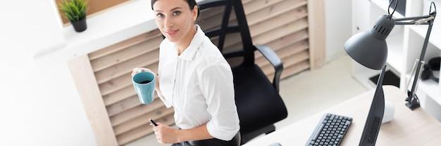 Uma jovem se sentou em uma mesa no escritório, segurando uma xícara e trabalhando