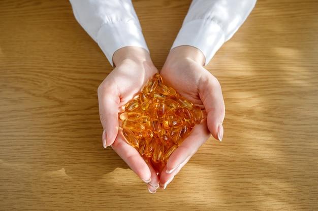 Uma jovem segura nas mãos um monte de cápsulas de óleo de peixe